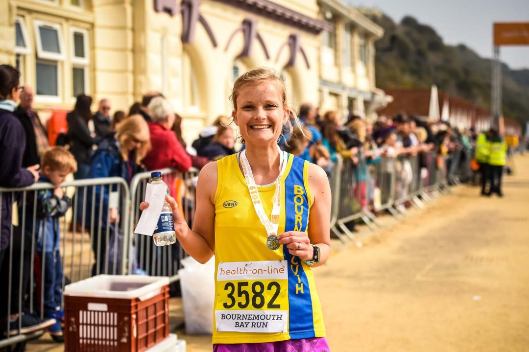 Woman smiling with her 2019 medal after the Bay run